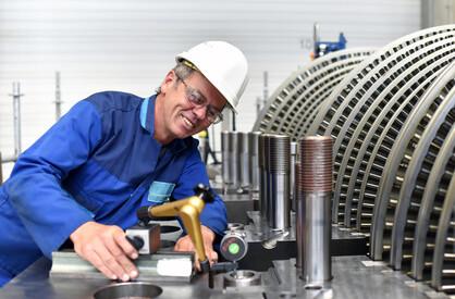 Monteur im Maschinenbau kontrolliert Mae einer Turbine