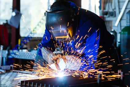 Welder bonding metal with welding device in workshop, lots of sparks to be seen, he wears welding googles